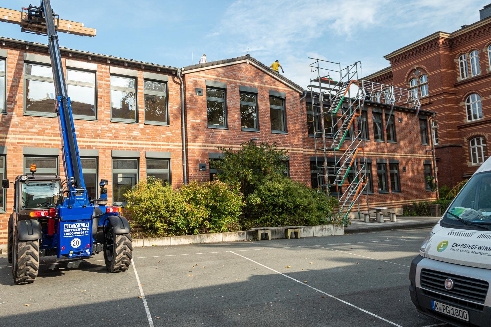 Gebäudeansicht vom Schulhof aus mit Gerüstturm für die Montage
