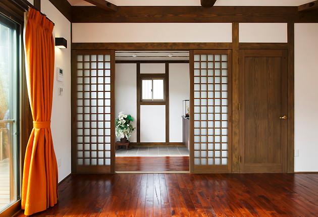 リビングから玄関をみる。整然とした佇まいに格子の建具が趣を加える。