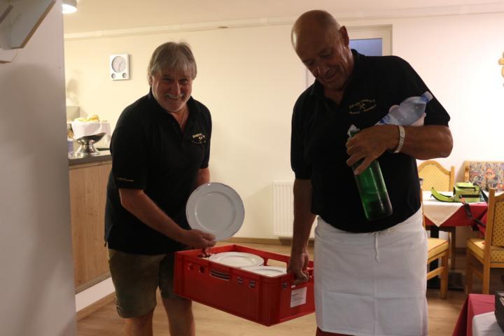 Georg und Heinz tragen die Teller zum Buffet