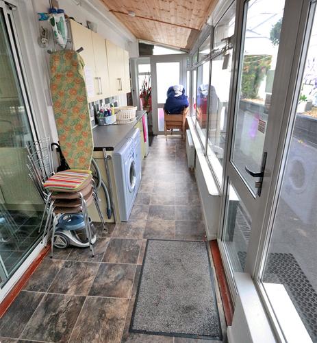 Vorraum zur Küche mit Waschmaschine und Ausgang zum Hof.