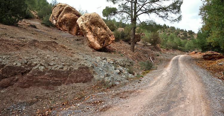 Felsblöcke, die sich aus dem oberen Abschnitt des Berges gelöst und ins Tal bewegt haben, liegen im labilen Gleichgewicht am Rande der Straße.