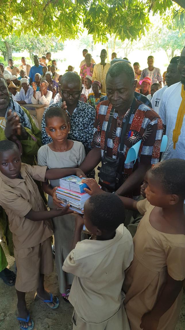 Schuldirektor Akpaki Kouami Aye'Founé verteilt im Dorf Kparioh gespendetes Schulmaterial an Kinder.