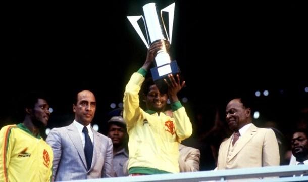 Théophile ABEGA, la capitaine des Lions indomptables, brandit le trophée sous les yeux de son coéquipier Ernest Ebongué et du Président Houphouet Boigny