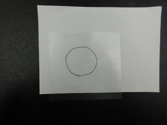 クリアファイル(透明な資料をはさむやわらかいプラスチックのシート)を一枚にしたものに絵を描きます。 机が茶色なので、見やすいように白い紙を置いてその上にクリアファイルを置いて絵を描きます。おおよその目安になるように、白い紙に丸を書いているのでその丸の中に入るくらいの絵を描きます。
