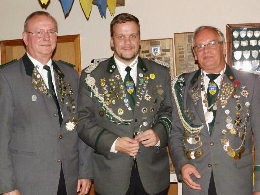"""Foto: Amtierender """"König der Wilden"""" Andreas Thiel (Mitte) mit dem Erbauer des Vogels Claus Mehrtens (links) und Sportleiter und Organisator des Vogelschießens Bruno Hensel (rechts)."""