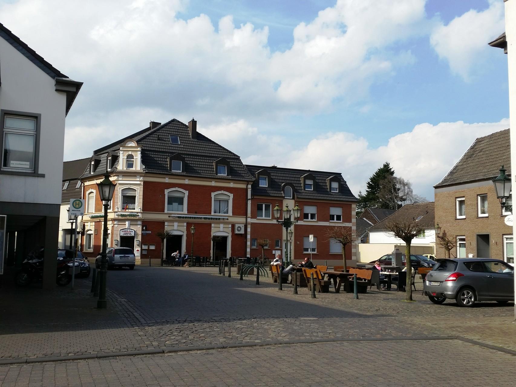 Kleiner Markt mit Brunnen und zwei Gaststätten mit Außengastronomie