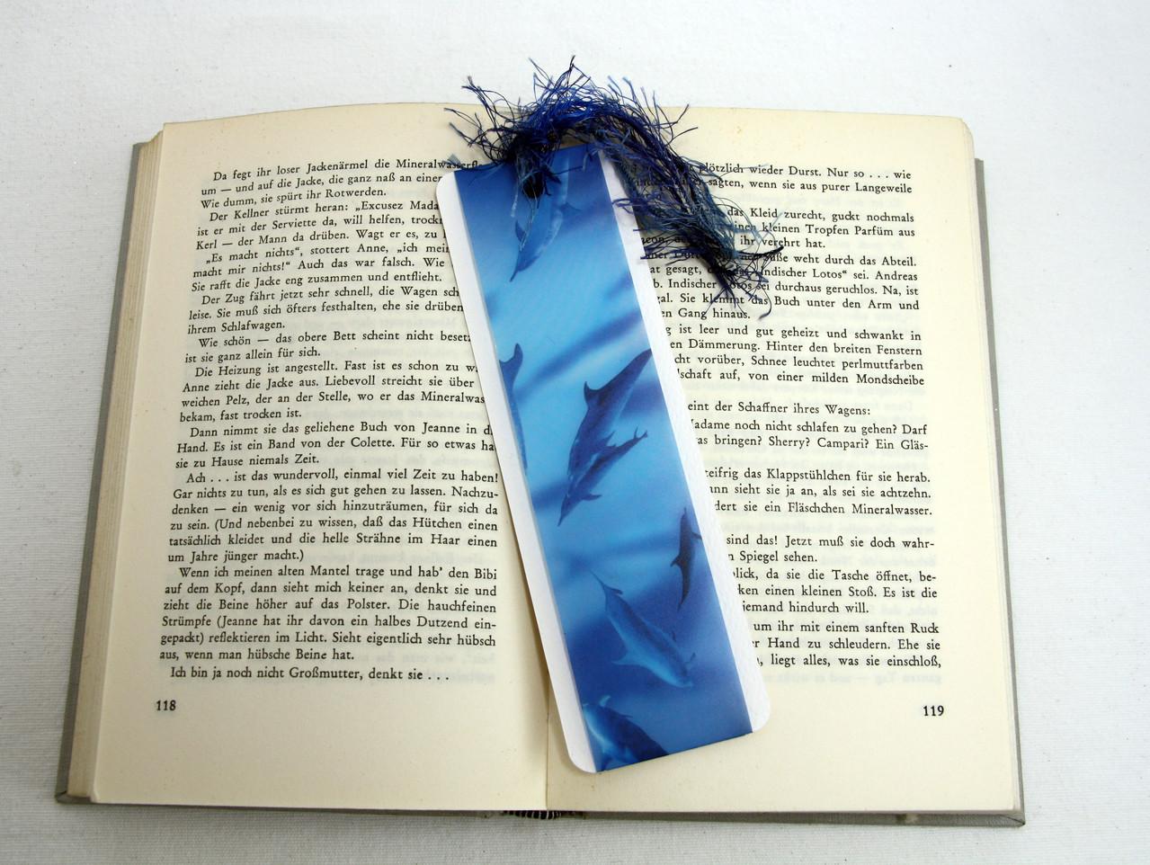 Lesezeichen aus weißem Tonkarton mit Delfinen auf Transparentpapier und blauem Polyestergarn