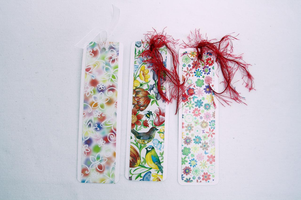 Lesezeichen links und rechts  aus weißem und bunt geblümtem leicht strukturiertem Tonkarton. Das mittlere Lesezeichen ist in Decoupage-Technik gefertigt. Es wurde eine weiße transparente Seidenschleife,sowie pinkfarbenes Polyestergarn verwendet.