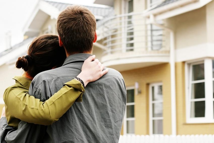 Bild von jungen Paar welches sich ein Haus von aussen anschauen.