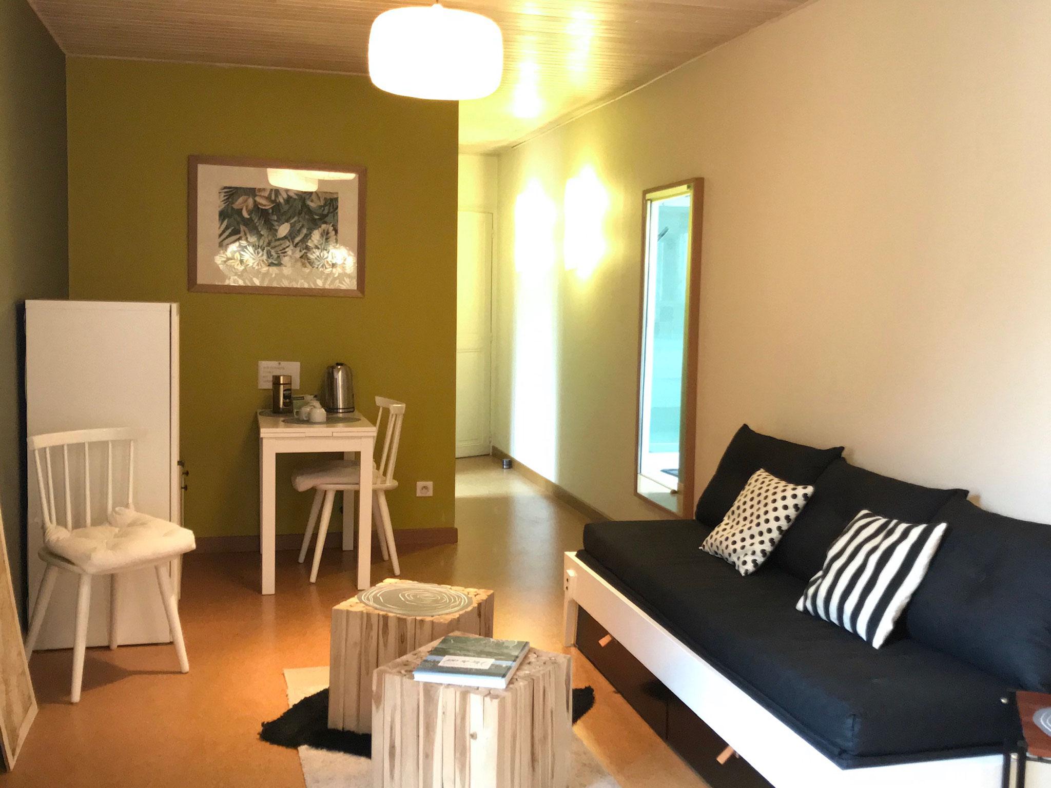 """Gîte """"Les Cépages"""", vue intérieure de la Chambre """"Chardonnay"""" : espace de vie (canapé convertible, table, minibar)"""
