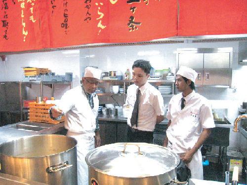 新しくオープンしたスクムビット20店で、スープをチェックする緒方会長(左)