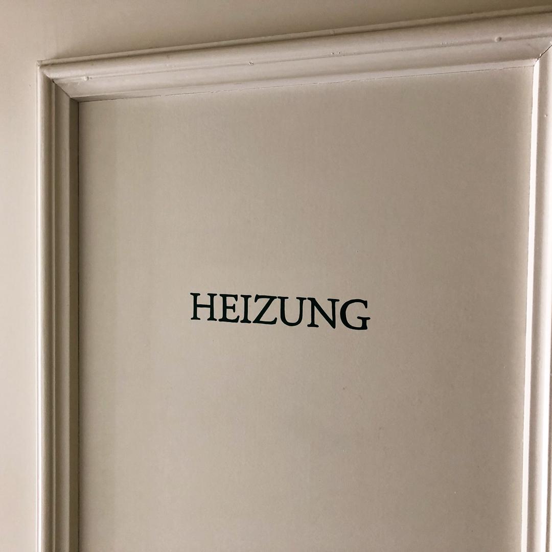Handgemalte Signaletik auf Türen von Mehrfamilienhaus - Heizung