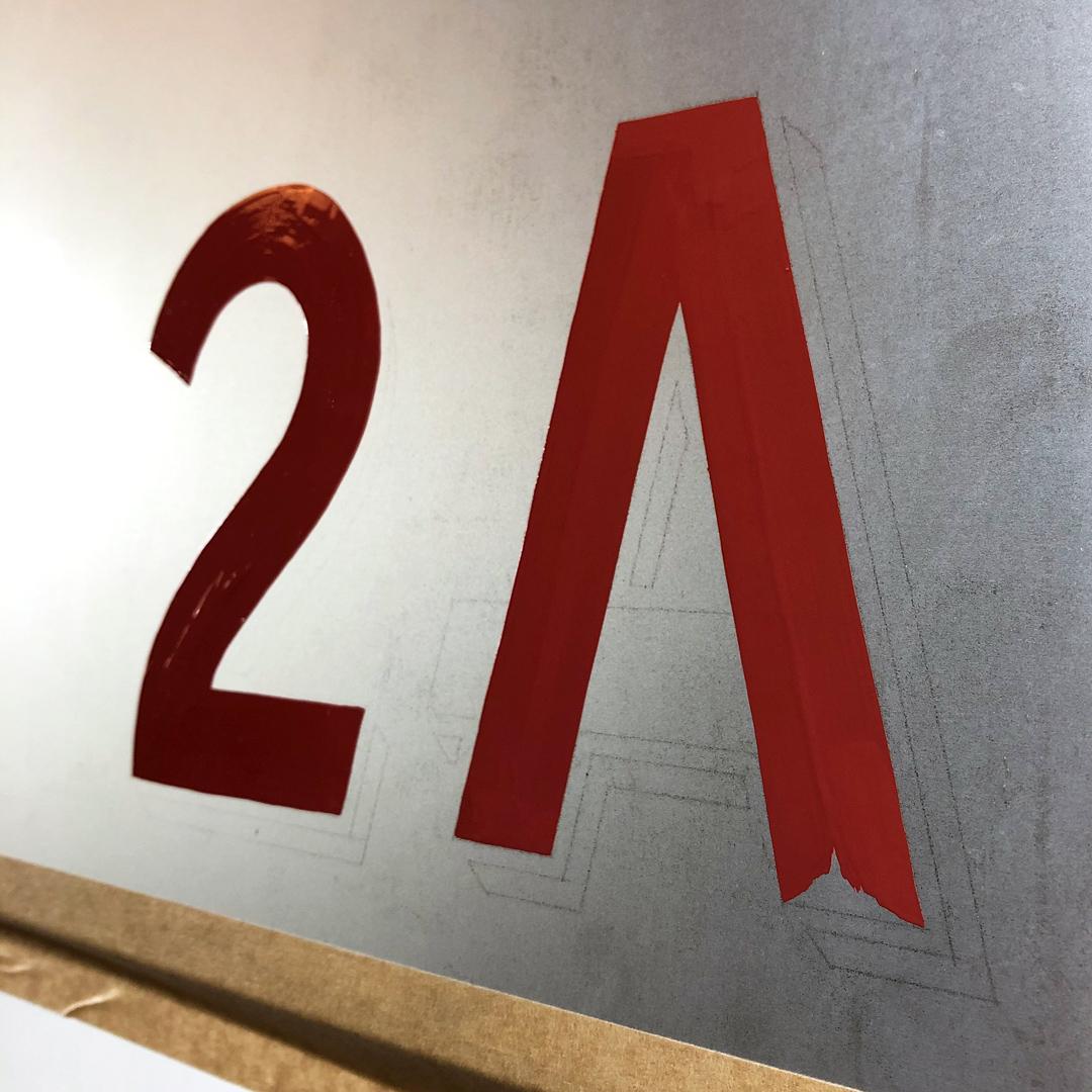 Handgemalte Hausnummer auf Briefkasten, passend zur Schriftenmalerei des Hausnamens.