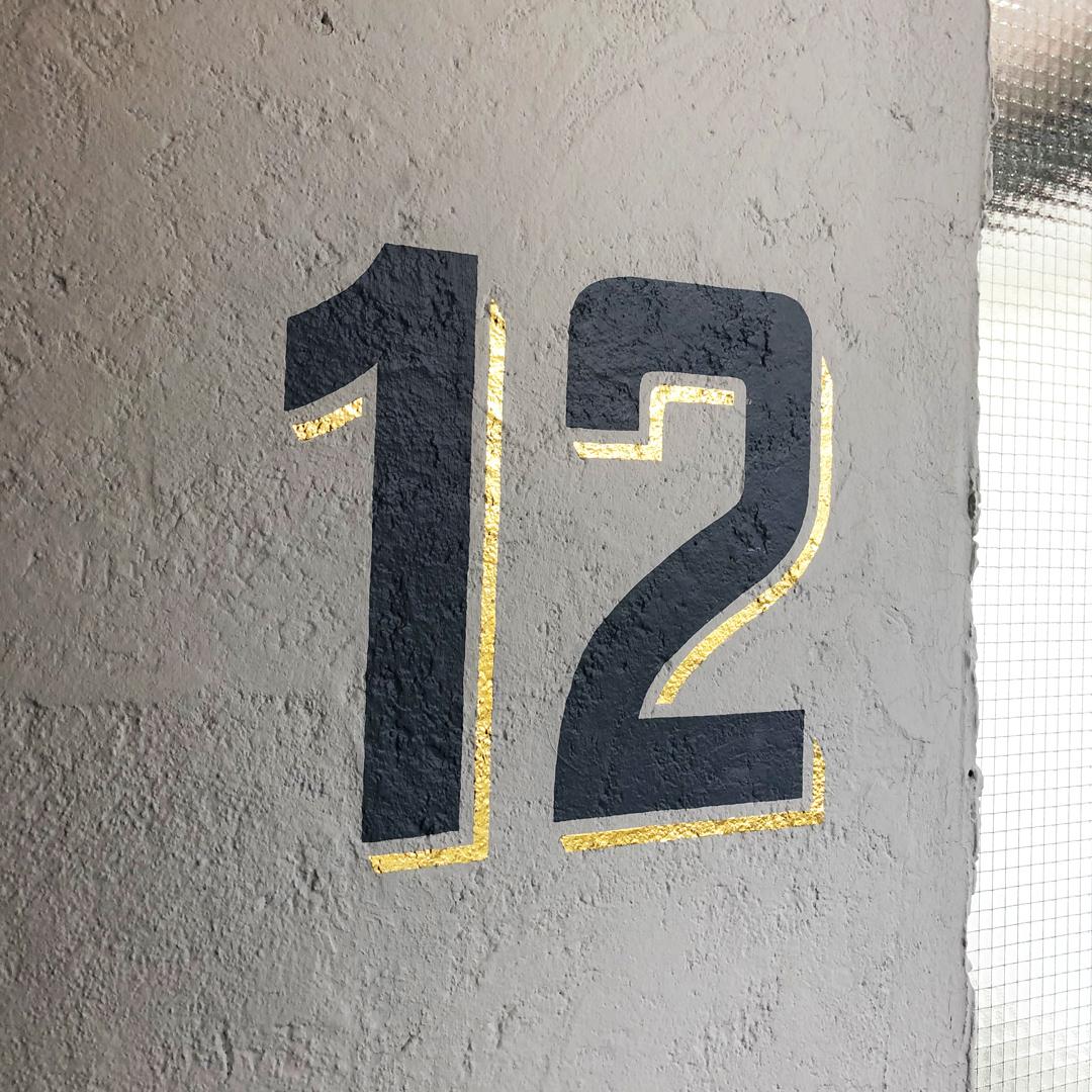 Handgemalte Hausnummer auf Wand von Hauseingang.