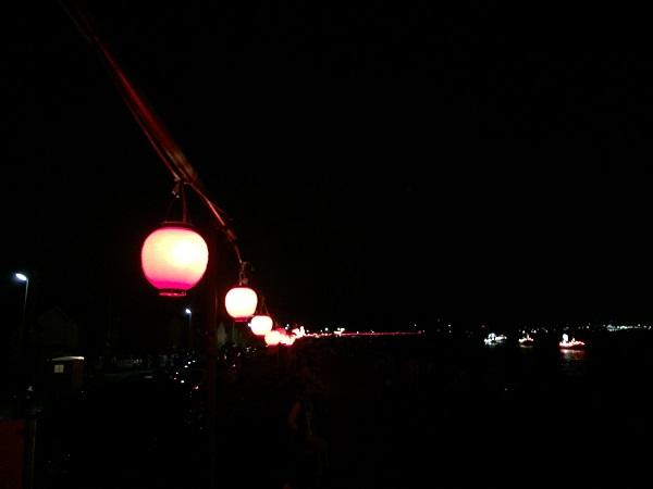 防波堤に沿って提灯が飾られます。海には光る漁船たち。