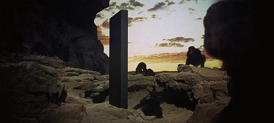 """Szenenfoto aus dem Film """"2001: Odyssee im Weltraum"""" von Stanley Kubrick (2001: A Space Odyssey, GB/USA 1968); der Monolith unter den Hominiden"""