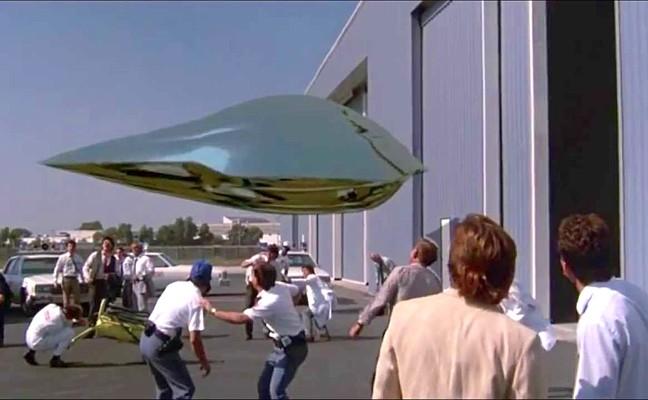 """Szenenfoto aus dem  Film """"Der Flug des Navigators"""" (Flight of the Navigator, USA 1986) von Randal Kleiser; das UFO am NASA-Hangar"""