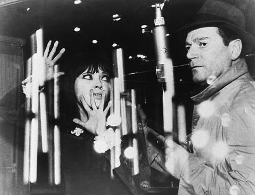"""Szenenfoto aus dem Film """"Lemmy Caution gegen Alpha 60"""" (Alphaville, Frankreich/Italien 1965) von Jean-Luc Godard; Anna Karina und Eddie Constantine"""