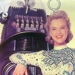 """Ann Francis und Robby the Robot in einem Pressefoto zu dem Film """"Alarm im Weltall"""" (Forbidden Planet, USA 1956) von Fred M. Wilcox"""