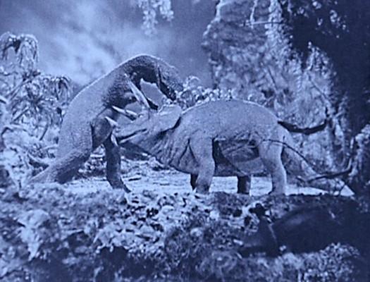 """Szenenbild aus dem Spielfilm """"Die verlorene Welt"""" (The Lost World, USA 1925) von Harry O. Hoyt und Willis O'Brien; ein Tyrannosaurus Rex und ein Triceratops"""