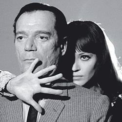 """Szenenfoto aus dem Film """"Lemmy Caution gegen Alpha 60"""" (Alphaville, Frankreich/Italien 1965) von Jean-Luc Godard; Eddie Constantine und Anna Karina"""