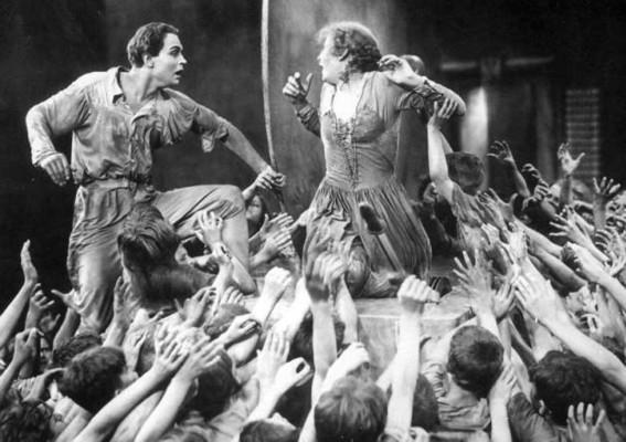 Metropolis (1927) Szenenfoto von Gustav Fröhlich und Brigitte Helm am Gong in der Arbeiterstadt, umringt von den Arbeiterkindern