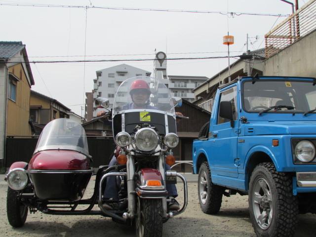 松居幹夫が愛車、ハーレーダビットソン1988年式サイドカーの運転席に乗り、こちらを向いている。横に写っているのが1990年式の幌付きジムニーだ。