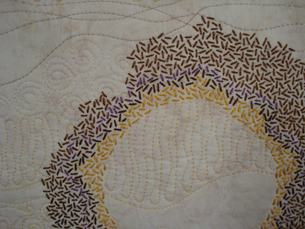 Close up of hand embroidery on a quilted wall hanging