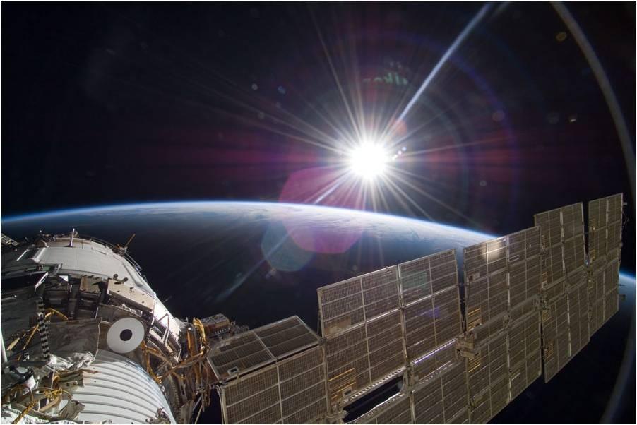 La Tierra en creciente y atrás el Sol, desde la Estación Espacial