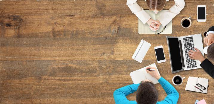 Drei Personen sitzen an einem Holztisch und diskutieren über Content wie Texte, Videos, Podcast oder Whitepaper