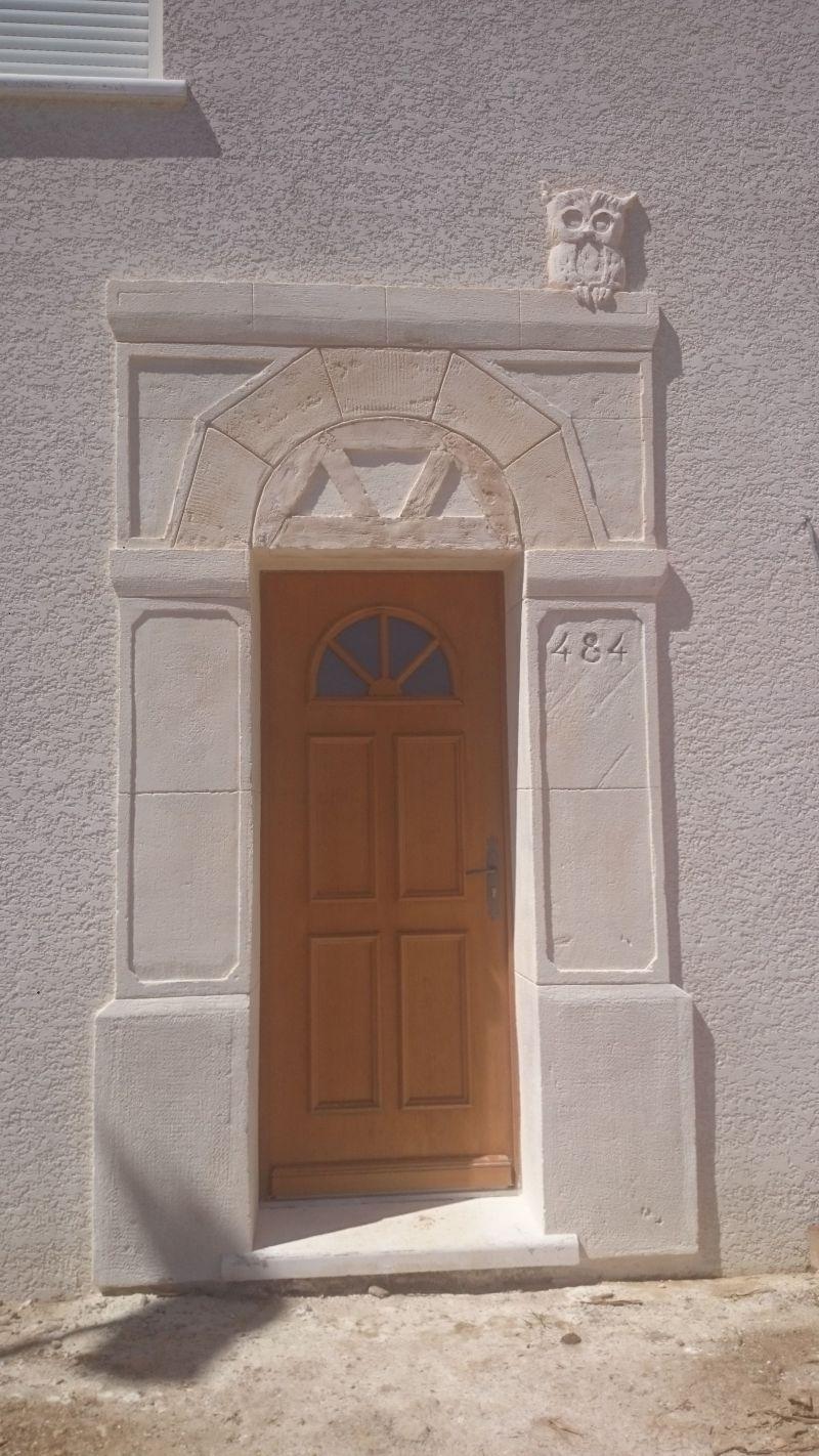 Porte d'entrée sculpté type pierre de taille avec décalages d'épaisseurs, jambage, faux bois et décoration hiboux