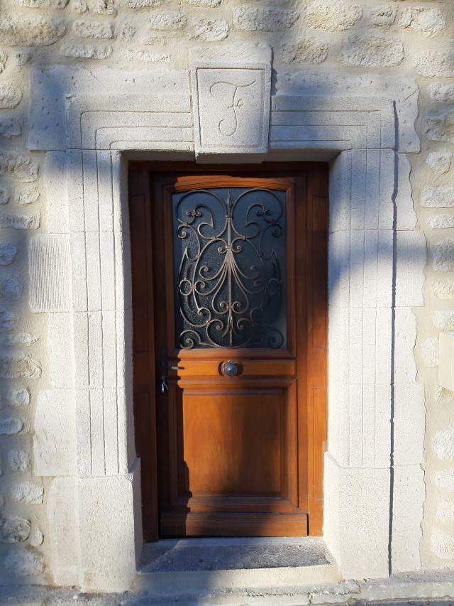 Enduit imitation pierre de taille sur porte d'entré et initiale de ses propriétaires sur clef de voute