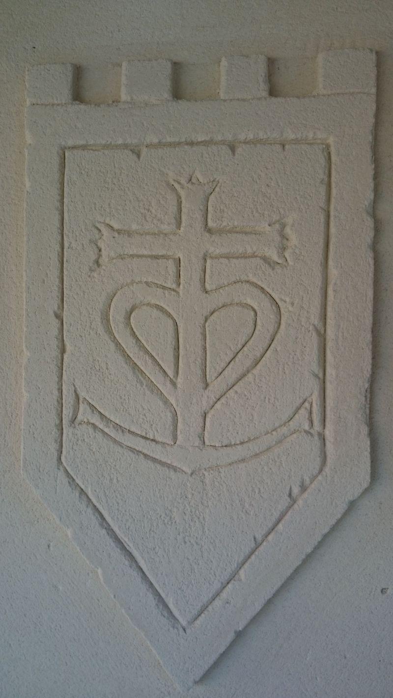 Sur mur terrasse, croix camarguaise sur son blason avec des remparts