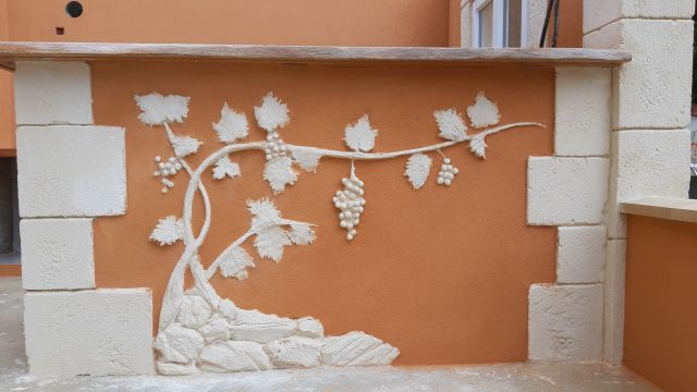 Sculpture d'une vigne avec ses feuilles et ses grappes de raisin, logé dans les pierres