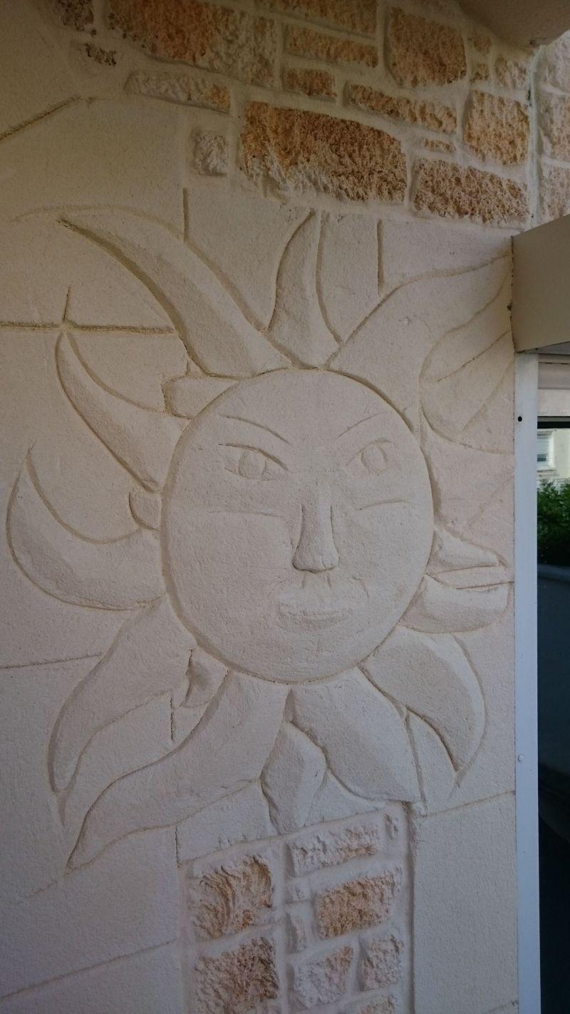 Soleil en enduit de façade sous hall d'entrée