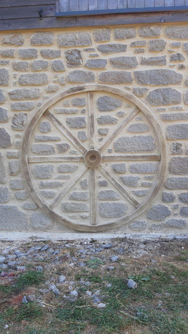 Roue de charette en enduit sculpté et structuré façon bois
