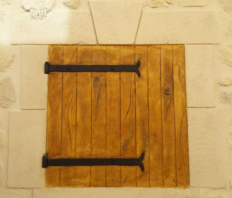 Volet bois en trompe l'œil avec ferrures et entourage pierre de taille sur abris de jardin