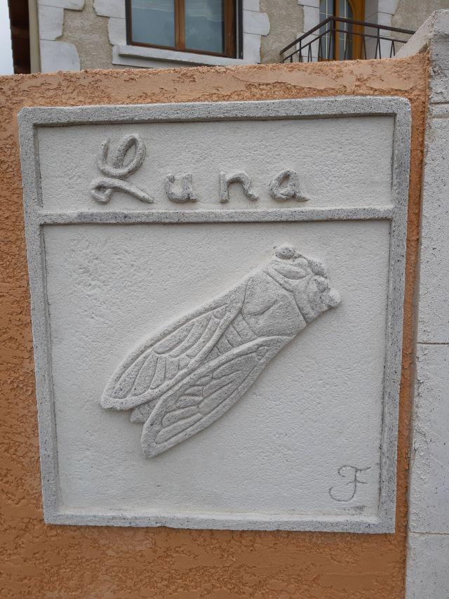 Nom de maison et cigale sculpté à l'entrée de la maison