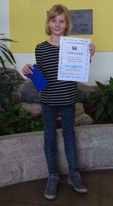 Sofie freute sich über eine Urkunde und einen Gutschein über 15,00 Euro, den sie nun für ein neues Buch einlösen kann.