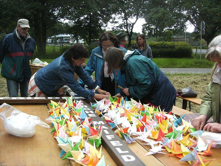 Viele helfende Hände befestigen die Origami-Kraniche am Friedenskreuz.