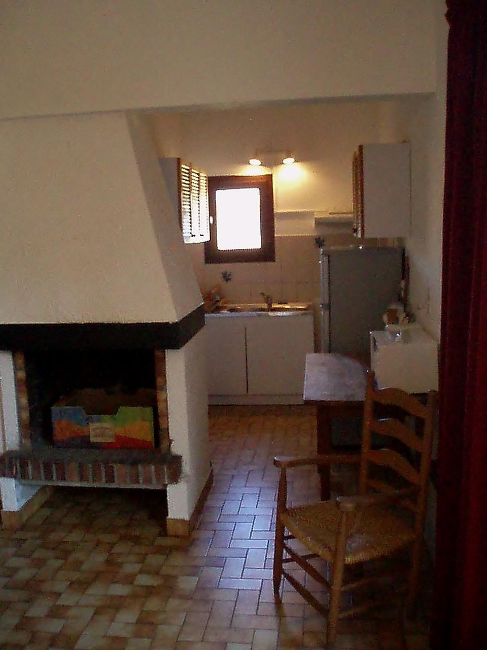 La cheminée et derrière, la cuisine.