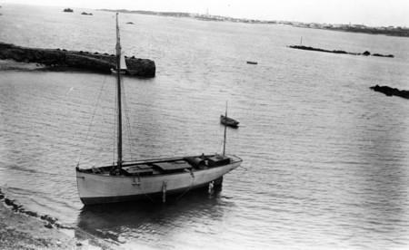 Le premier Plutéus , construit en 1905, au port du Vil à Roscoff photographié depuis une fenêtre du laboratoire, le long de la cale on aperçoit un bateau de passage de l'île de Batz
