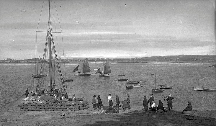 L'activité maritime de port blanc vers 1920, un dundée caboteur charge des sacs de pommes de terre, deux sloups de pêches ont leur voiles hissées et sont prêt à partir, les petits canots sont certainement des goémoniers (Collection Lacombe AD22)