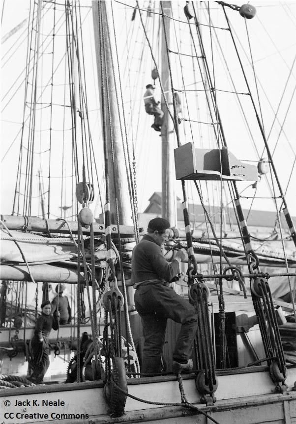 Un matelot de la goélette la Bretonne  repeint en blanc les amarrages en fil de fer galvanisé des haubans, au second plan à bord d'une autre goélette un matelot assis sur une chaise de calfat gratte le mât (Photo Jack K. Neale)