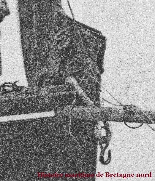 Le crochet de corps-mort et son estrope fourrée capelée sur l'étrave et le bout dehors traversant la préceinte