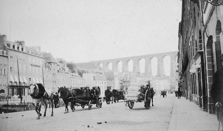 Morlaix quai de Léon, le transport hippomobile est important en ville, un « camion » à petite roues, tiré par deux chevaux est chargé de tonneaux, croise une charrette chargée de sacs