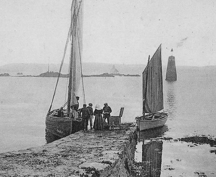 La cale de base mer à l'entrée de port-clos à Bréhat, un sloup de passage et un canot à misaine  Le vent est bien faible, dans le canot le gouvernail est démonté et la godille dont le trou de godille est dans l'axe du tableau