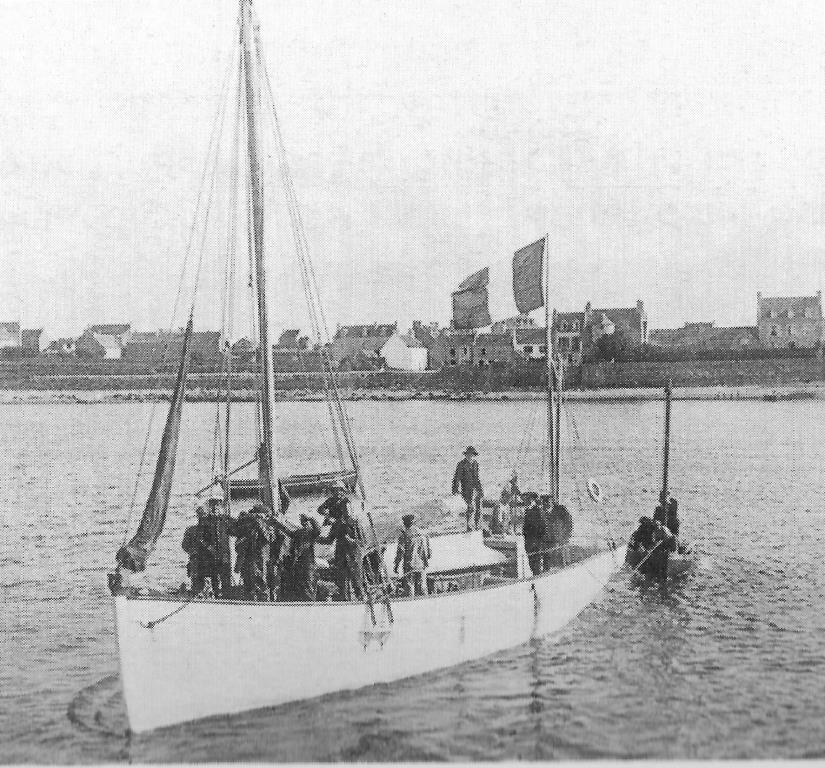 Le Pluétus manœuvrant dans le port de Roscoff, avec un grand nombre de personnes à bord, son canot annexe est amarré à l'envers sur son roof