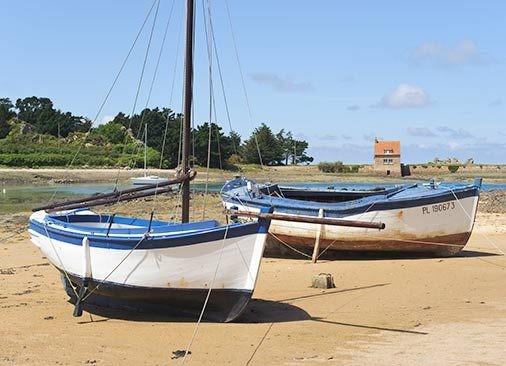 Petit cotre du Trégor et canot de pêche en bois désarmés dans l'anse de Buguelès (photo : photolegende.com)