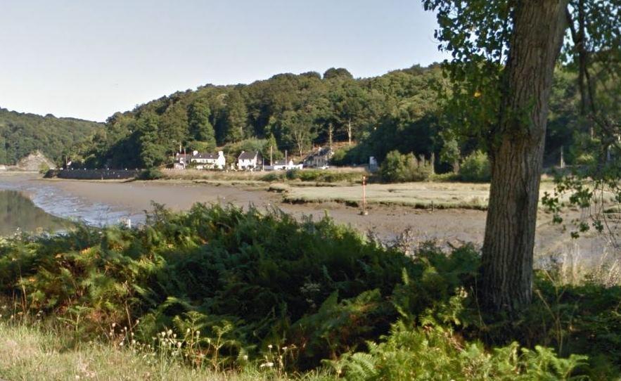 La vue de route par l'outil en ligne Google Maps a permis d'identifier  le lieu  avec  certitude par la maison du coté de la rive trégoroise de la rivière et par les rochers de l'autre rive